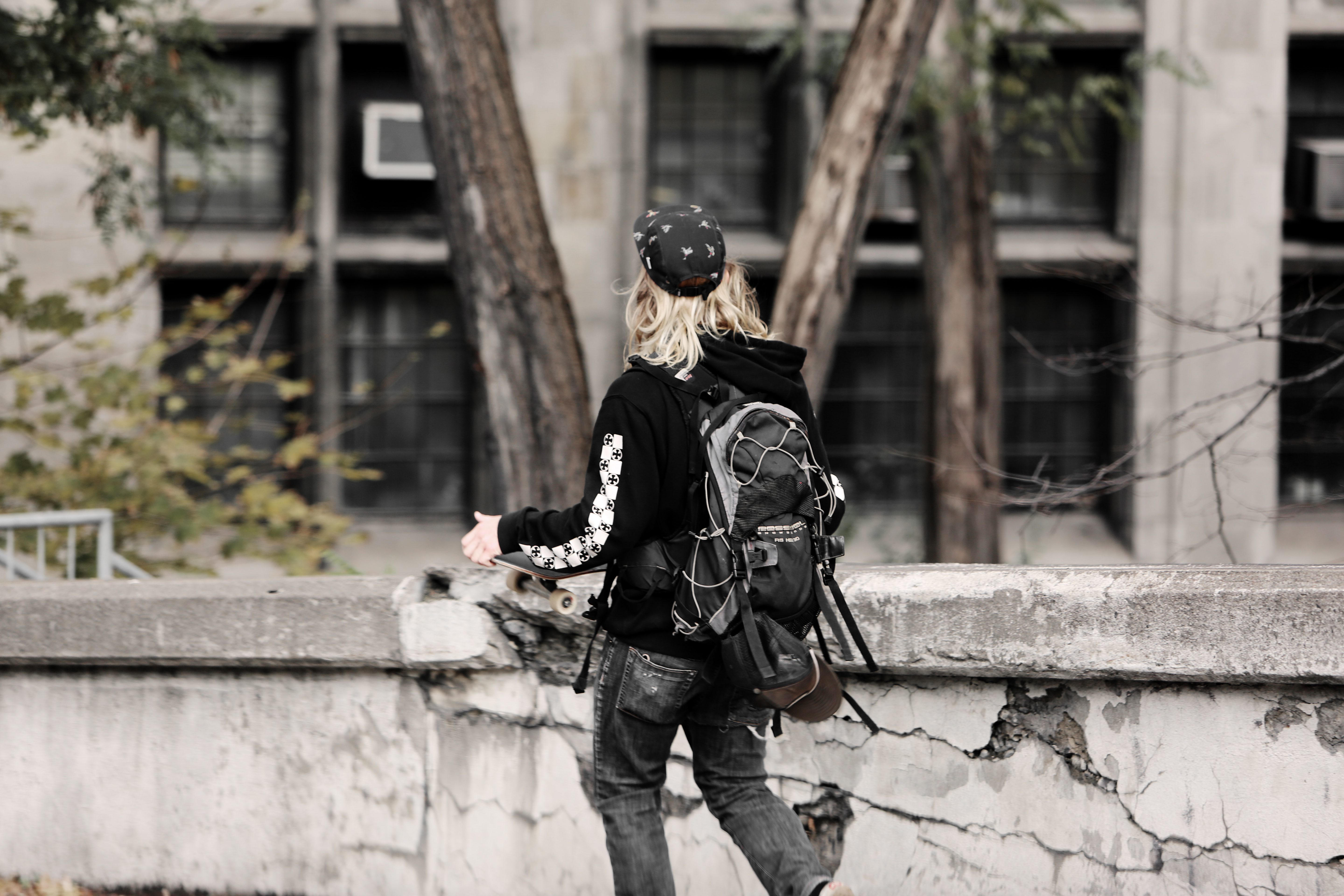 Teenager with long blonde hair, backpack and skateboard walking away from the camera