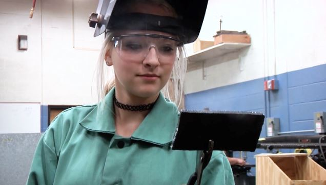 student with a welding mask