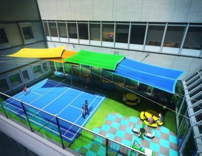 Picture of planned courtyard, viewed from above. A blue tennis court, checker-patterned pavement, grass, coloured awnings, and picnic tables and seats are visible. Click to visit the Project's website.